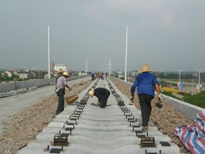 Some workers are inspecting the railway that is under construction, rubber pads are installed above the concrete sleeper.